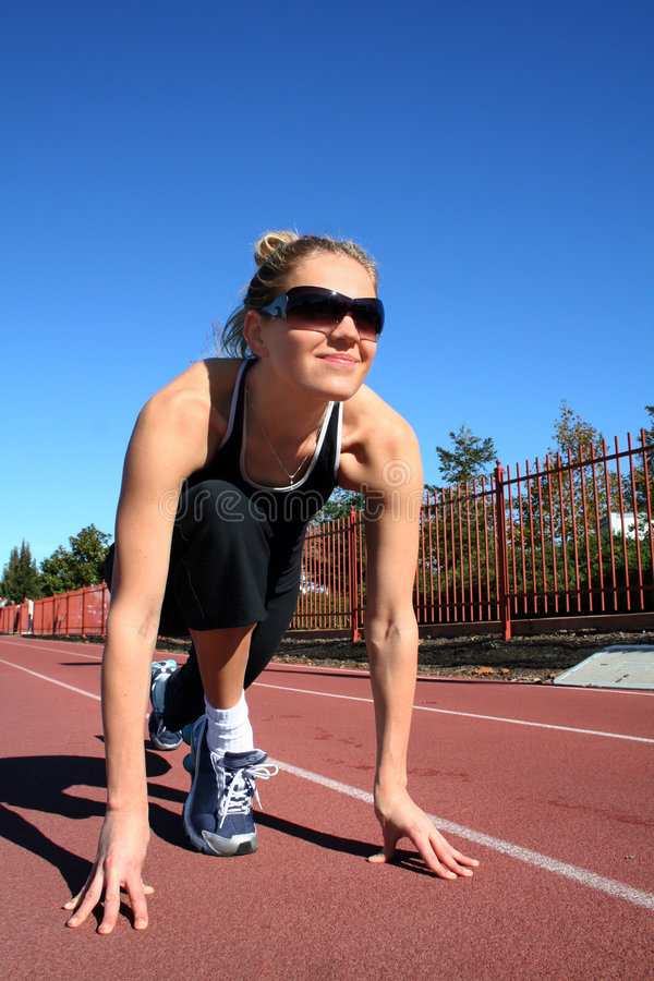 Exercising woman. Young pretty woman exercising on a racetrack stock photos