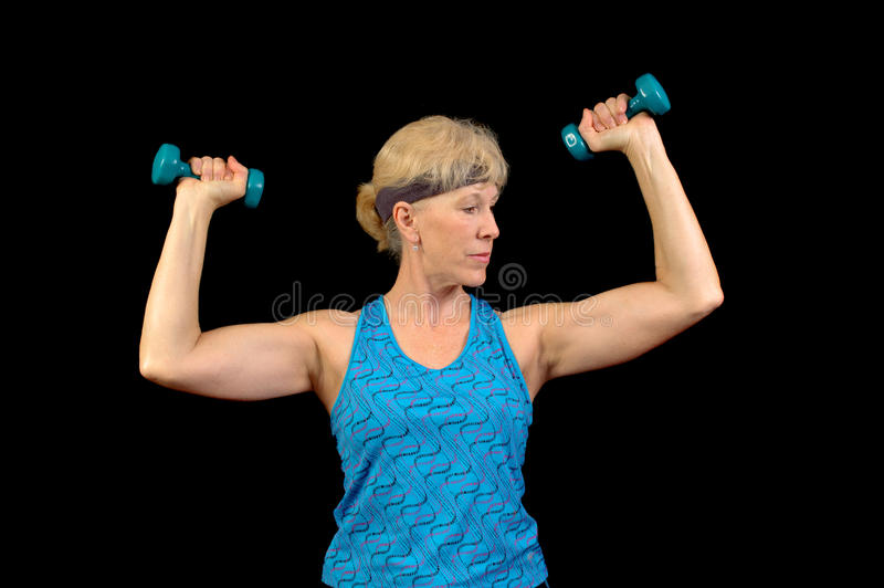 Exercising woman. Attractive baby-boomer exercising with weights isolated over black stock photos