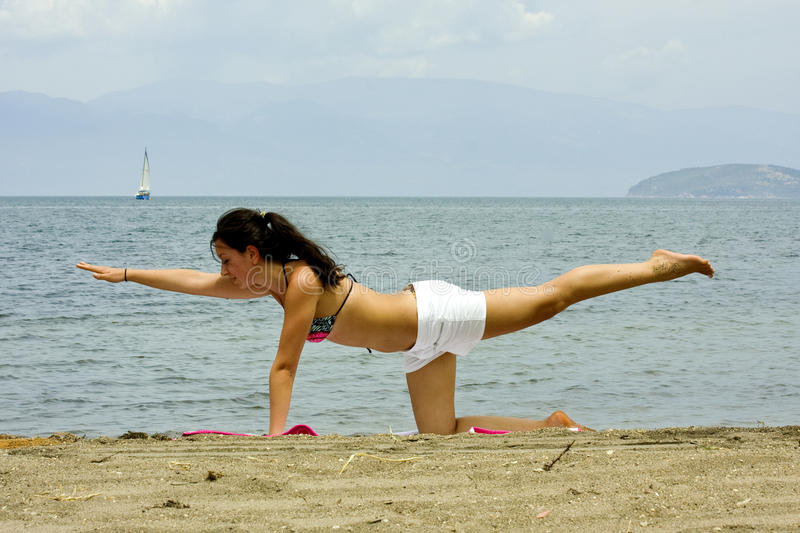 Exercising woman on the beach stock photography