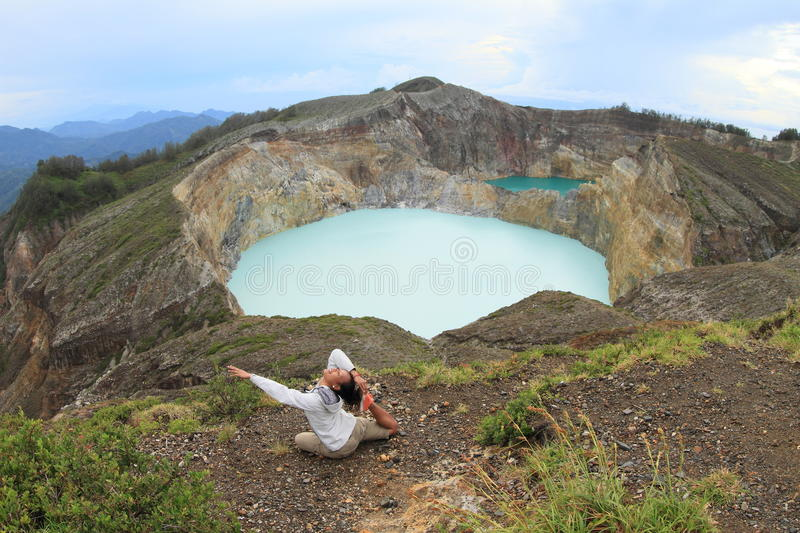 Exercising yoga on volcano. Papuan young woman exercising yoga Mermaid pose in front of light blue or white acid-saline lake Tap - Tiwu Ata Polo - and dark green