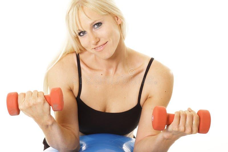 Exercitador que sorri com dumbbells fotografia de stock royalty free