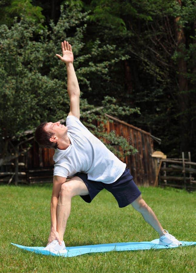 Exercitando a ioga no parque - Pose prolongado do ângulo lateral imagens de stock royalty free