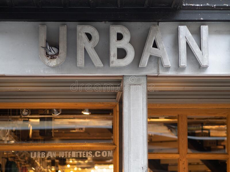 EXETER, UNITED KINGDOM - NOVEMBER 6 2019: Urban Outfitters shop front sign in Exeter city centre with a pigeon nesting in the firs. T sign letter. Open retail royalty free stock photos