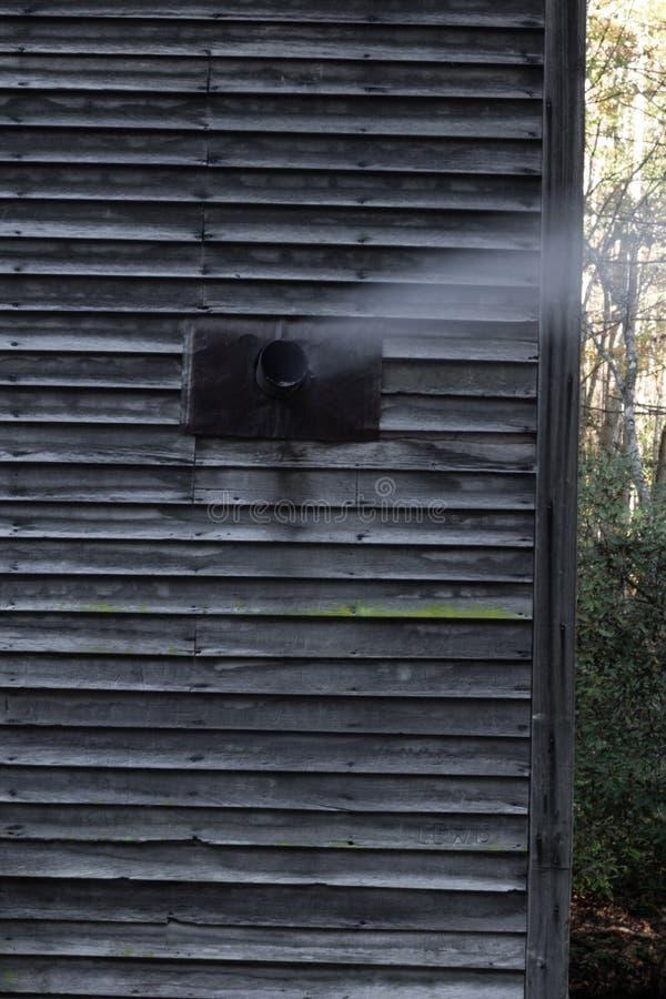 Exhalez dans le côté de la vieille carlingue en bois avec de la fumée d'un fourneau en bois intérieur photo libre de droits