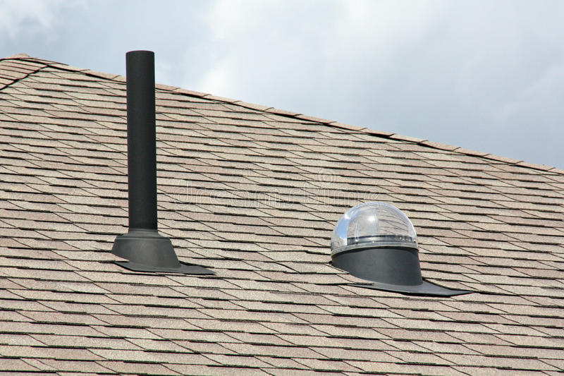 Exhaust vent and skylight. An exhaust vent and skylight side by side on a shingled roof stock image