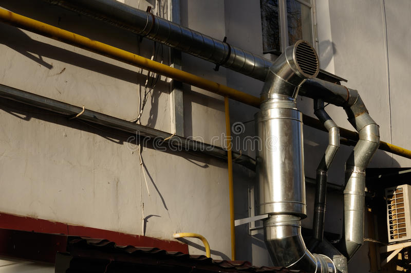 Exhaust Ventilation Pipe on Building. An exhaust ventilation pipe and other pipes on a building stock images