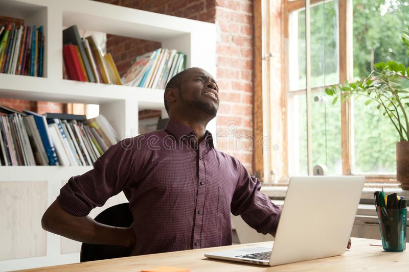 Exhausted african american male office worker having back discom royalty free stock photos