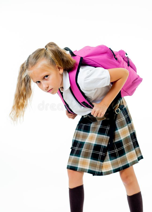 Exhausted beautiful little schoolgirl carrying a big schoolbag royalty free stock image