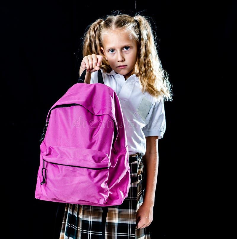 Exhausted beautiful little schoolgirl carrying a big schoolbag stock photography