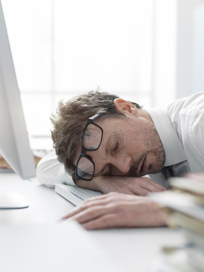 Exhausted business executive sleeping on his desk royalty free stock photos