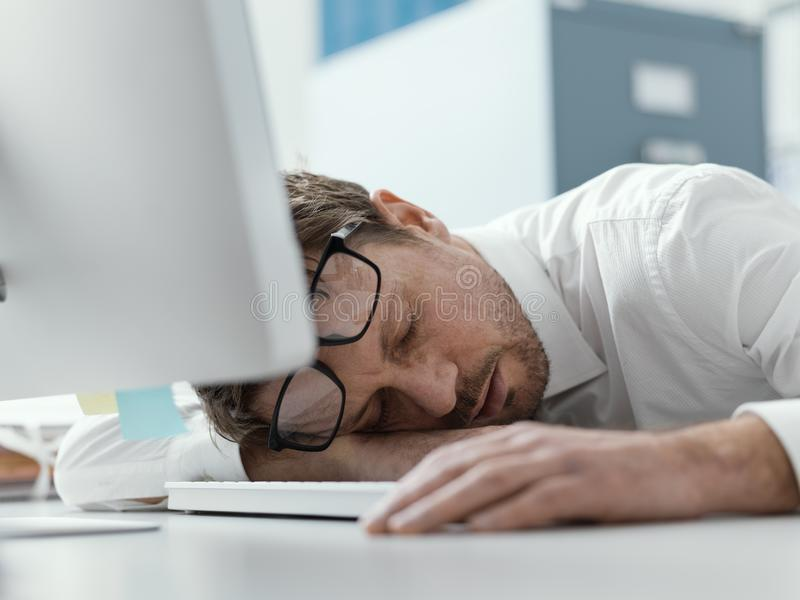 Exhausted business executive sleeping on his desk stock photo