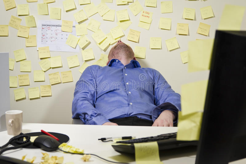 Exhausted Businessman. A exhausted / tired business man with his head backwards. Many notes in the background stock photography