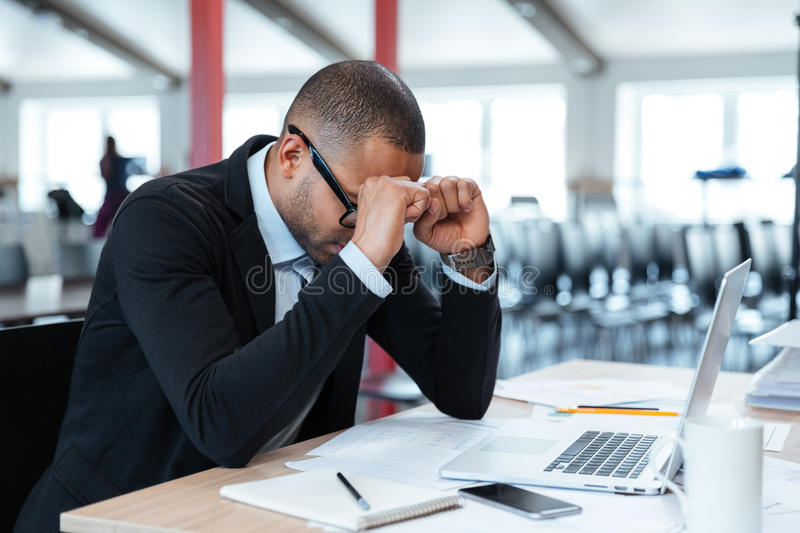 Exhausted businessman at his desk royalty free stock photography