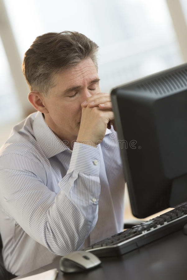 Exhausted Businessman Leaning On Computer Desk Royalty Free Stock Images