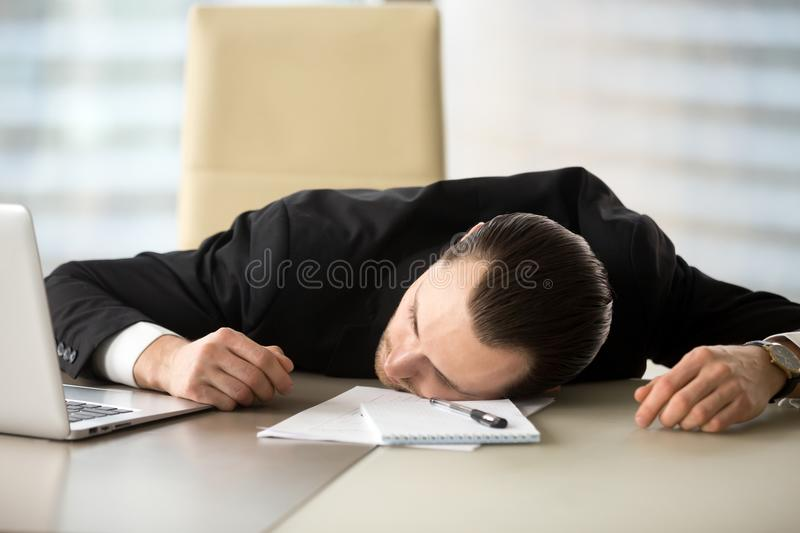 Exhausted businessman passed out at his work desk in office. Exhausted businessman passed out at workplace desk in office. Tired entrepreneur laying on his desk stock image