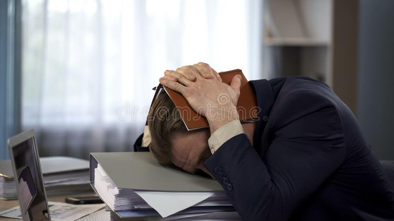 Exhausted businessman putting notebook on head at workplace, deadline pressure royalty free stock image