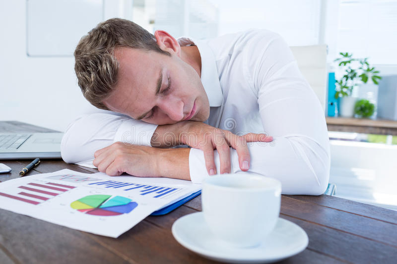Exhausted businessman sleeping on the desk. In the office royalty free stock image