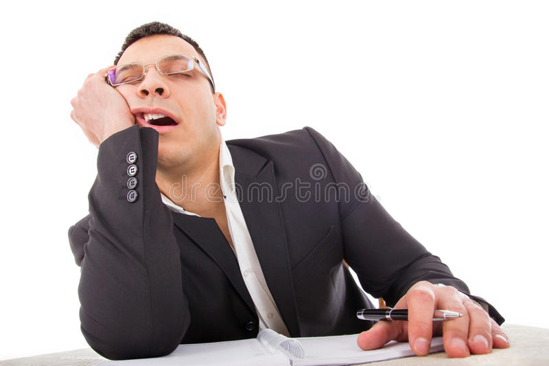 Exhausted businessman sleeping at his desk yawning. With pencil in hand stock photo
