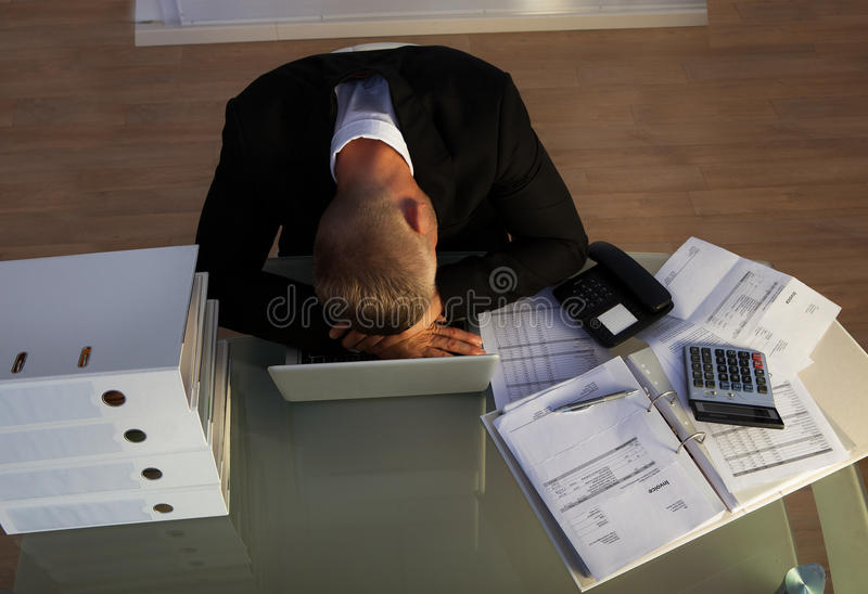 Exhausted businessman sleeping an a stack of files. As he works late stock photography