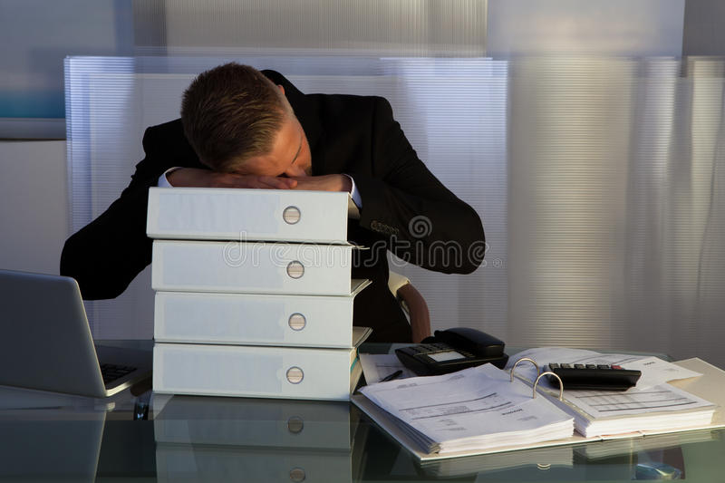 Exhausted businessman sleeping an a stack of files. As he works late stock images
