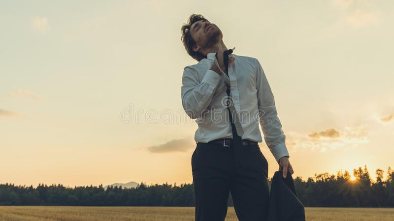 Exhausted businessman standing in nature. Under an evening sky untying his tie relaxing the stress stock photography