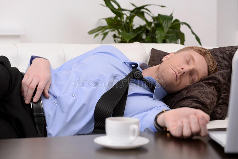 Exhausted businessman. Young tired businessman in formalwear sleeping on the couch stock photography