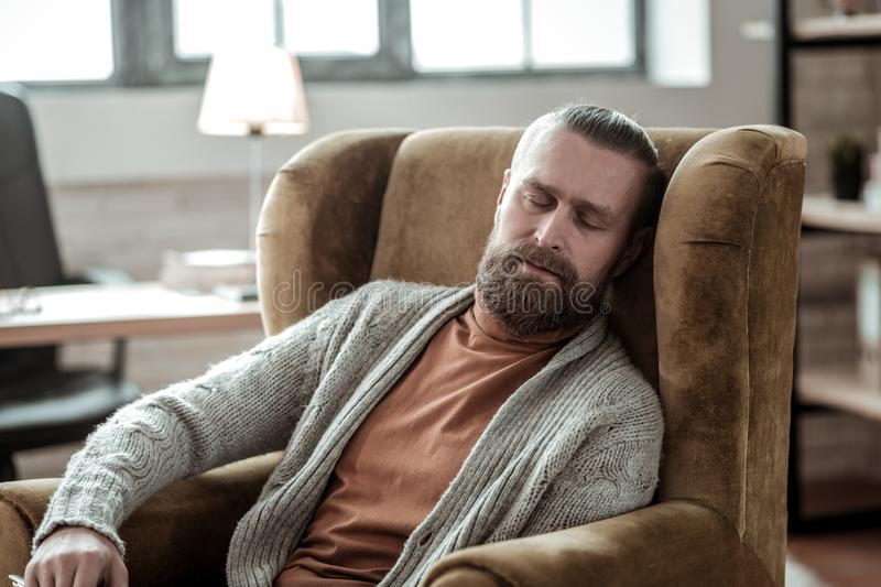 Exhausted counselor falling asleep in his armchair at work royalty free stock photos
