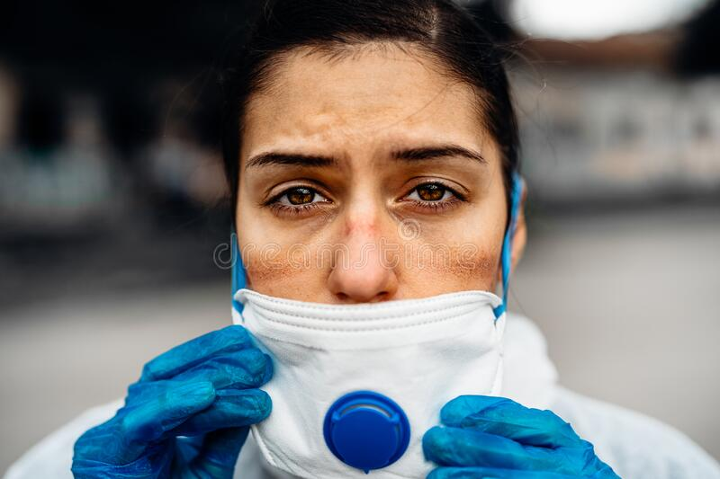 Exhausted doctor/nurse wearing coronavirus protective gear N95 mask uniform.Coronavirus Covid-19 outbreak.Mental stress of. Frontline worker.Face scars.Mask stock photos