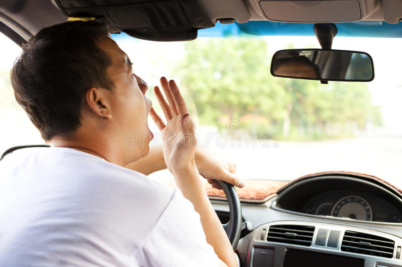 Exhausted driver yawning and driving car. On the road royalty free stock photos