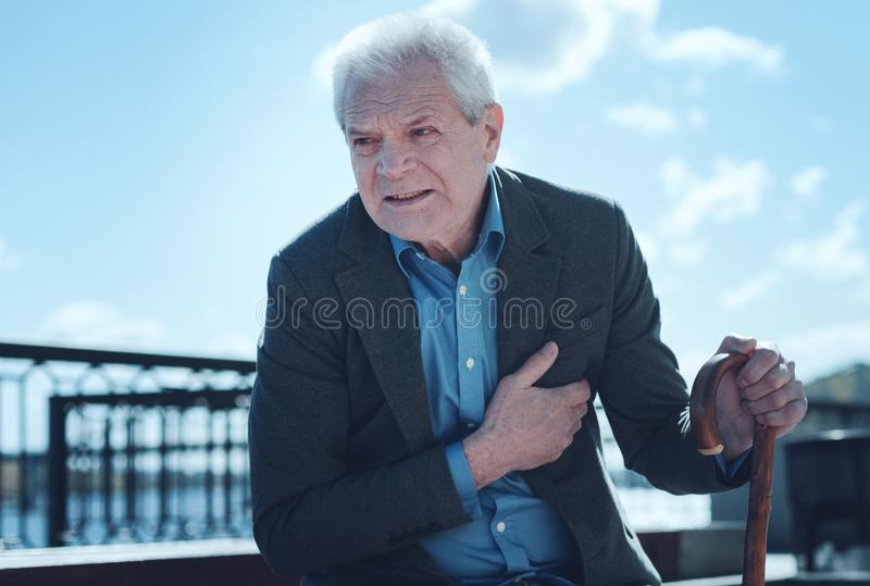 Exhausted elderly man feeling pain in heart area. It hurts a lot. Frustrated senior man looking into vacant space while holding her hand on a chest and suffering stock photography