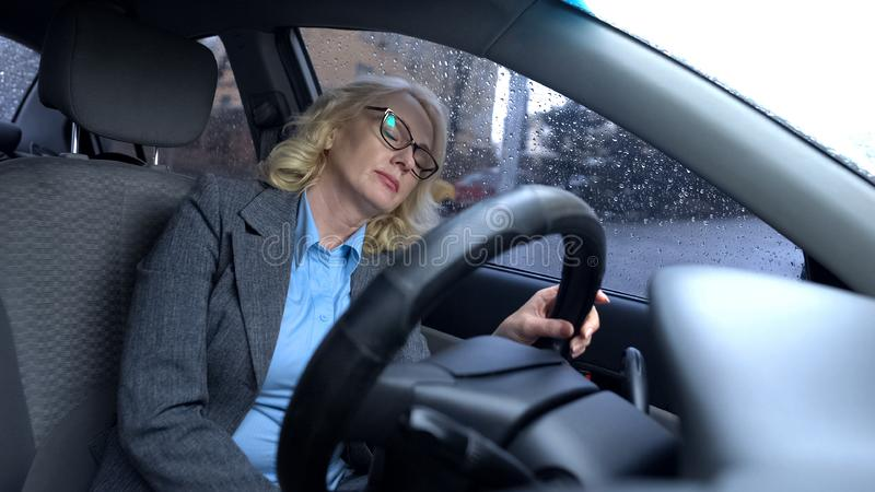 Exhausted elderly woman sleeping in car, rain drops window, busy urban lifestyle. Stock photo royalty free stock image