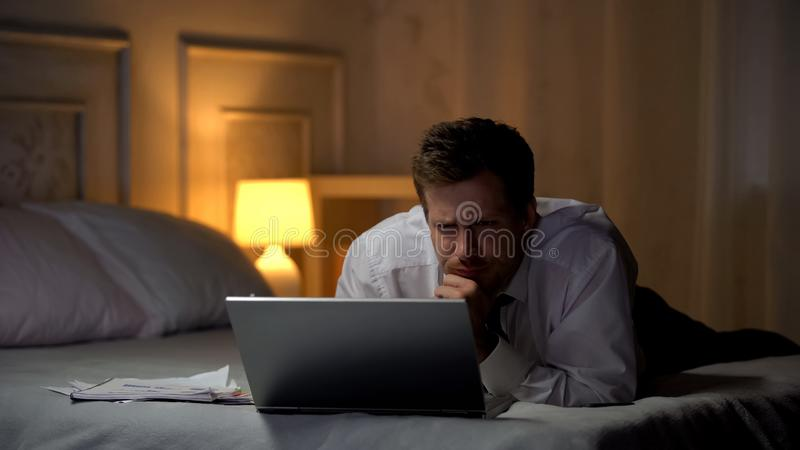 Exhausted engineer lying on bed, working on laptop at night, reading mail royalty free stock photos