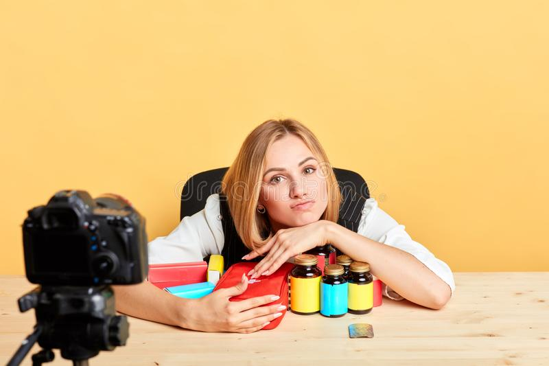 Exhausted female nutritionist grabs bunch of diverse vitamins and supplements. Isolated shot of exhausted young female nutritionist posing in front of camera stock photography