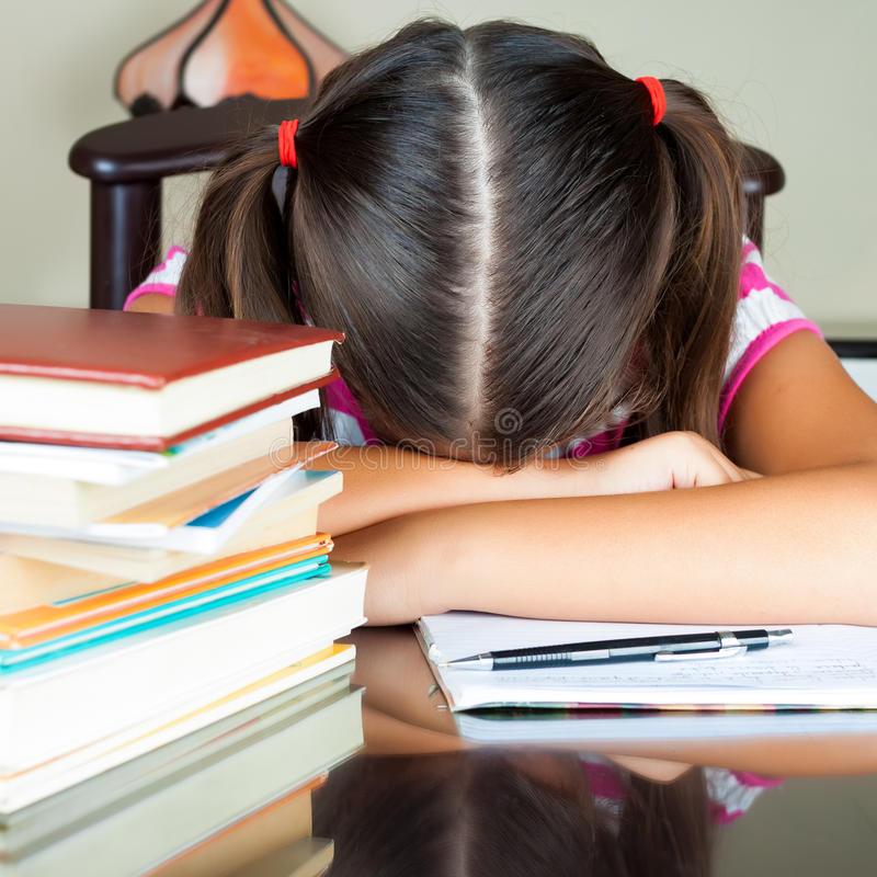 Exhausted girl sleeping on her desk. After studying too much (there are books on the desk stock images
