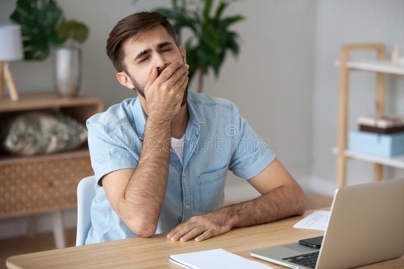Exhausted male worker yawn at workplace feeling unmotivated stock image