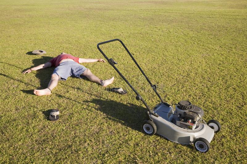 An Exhausted Lawn Mowing Man. An exhausted man lying on the ground collapsed after mowing a huge lawn royalty free stock photo