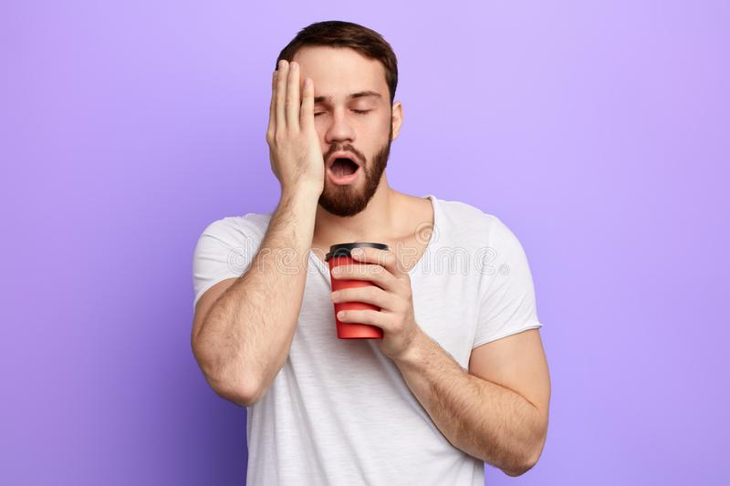 Exhausted man with wide open mouth and closed eyes holds fresh beverage. Displeased tired man with wide open mouth and closed eyes holds fresh beverage in stock image