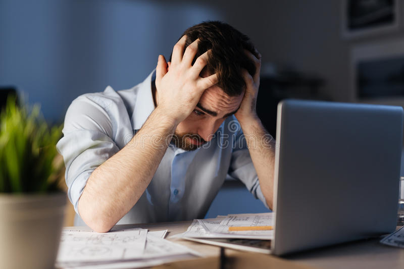 Exhausted Man Working Extra Hours in Night Office. Portrait of exhausted man working overtime with documentation and laptop alone in dark office late at night stock photos