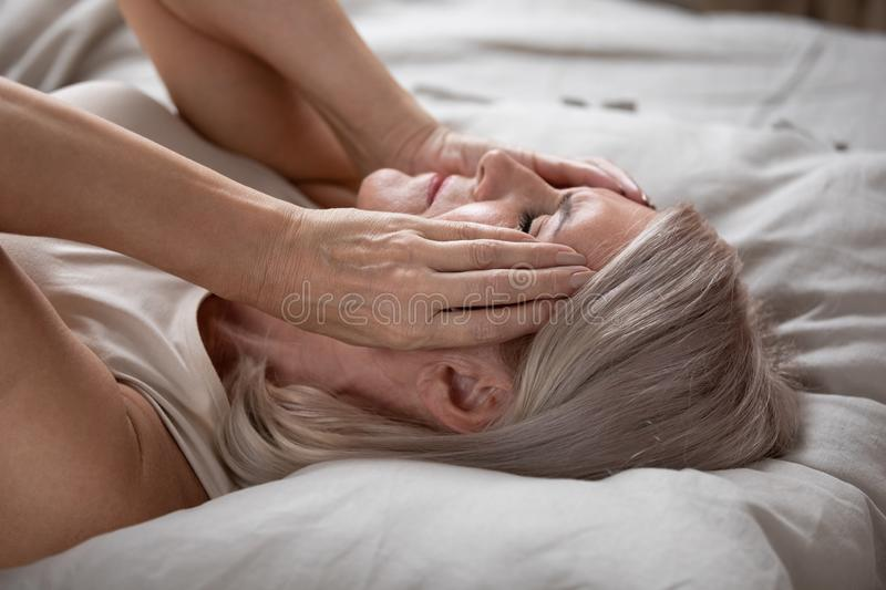 Exhausted mature woman lying in bed, touching temples close up. Unhappy exhausted mature woman with closed eyes lying in bed, touching temples close up, tired stock photography