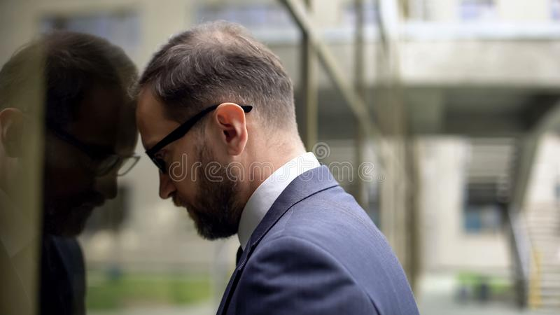 Exhausted office worker in suit leaning on glass building wall, depression. Stock photo stock photography