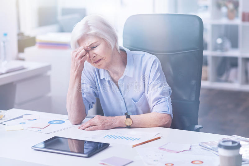 Exhausted office worker wrinkling her forehead. Need a vacation. Tired mature female sitting at the table holding her arms on her work place while touching stock image
