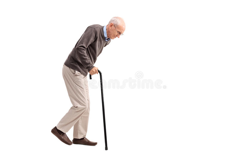 Exhausted old man walking with a cane. Studio shot of an exhausted old man walking with a cane isolated on white background royalty free stock images