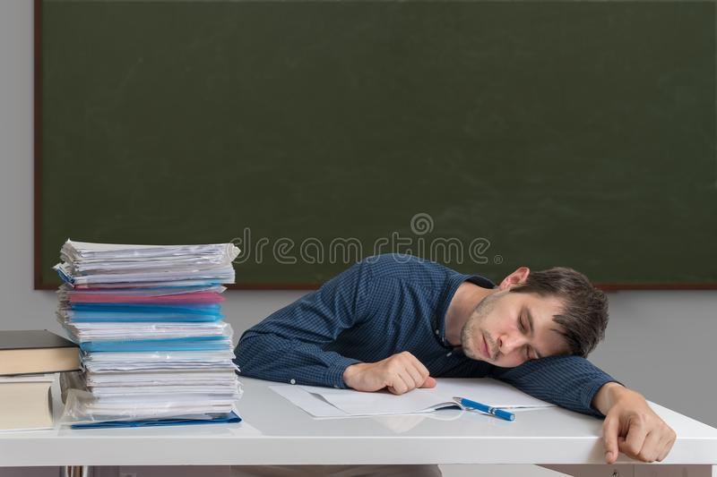 Exhausted and overworked teacher is sleeping on desk in classroom stock photo