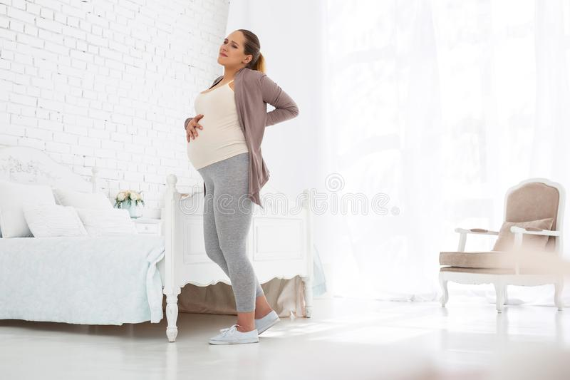 Exhausted pregnant woman suffering from back pain stock images