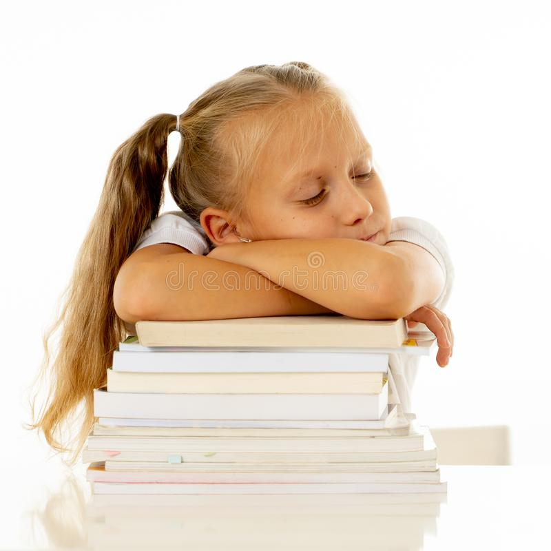Exhausted schoolgirl falling asleep on her books after studying too much royalty free stock images