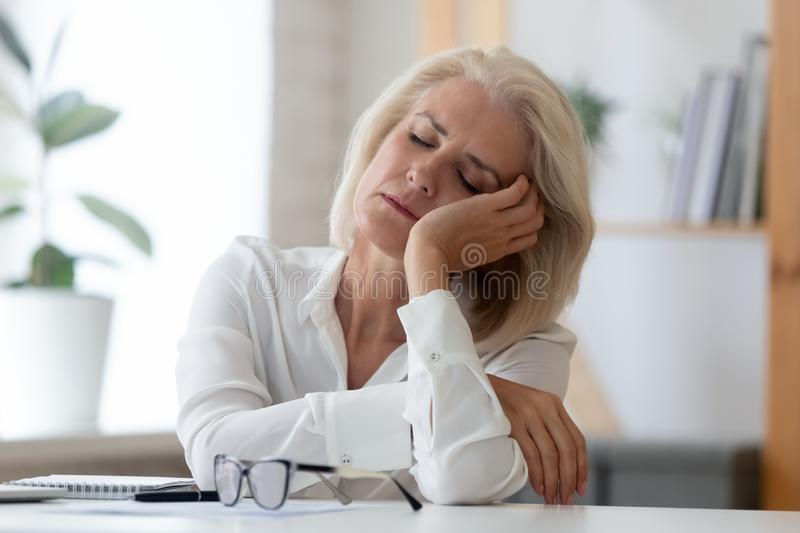 Exhausted senior businesswoman fall asleep at workplace royalty free stock photography