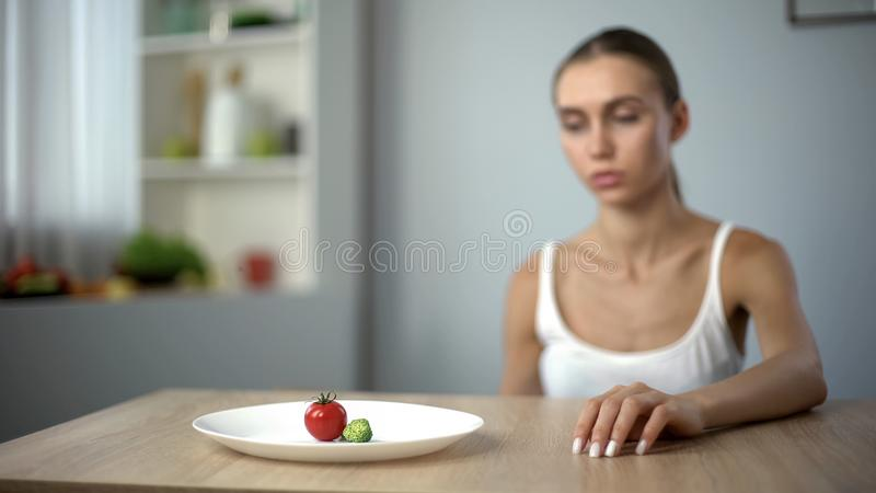 Exhausted slim woman looking at small portion of breakfast, self-destruction royalty free stock photo