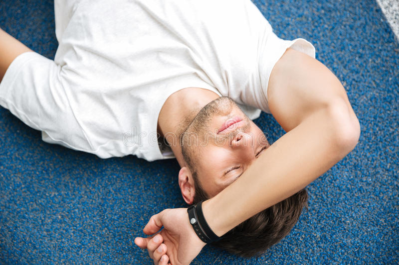 Exhausted sportsman finished his race and resting royalty free stock photos