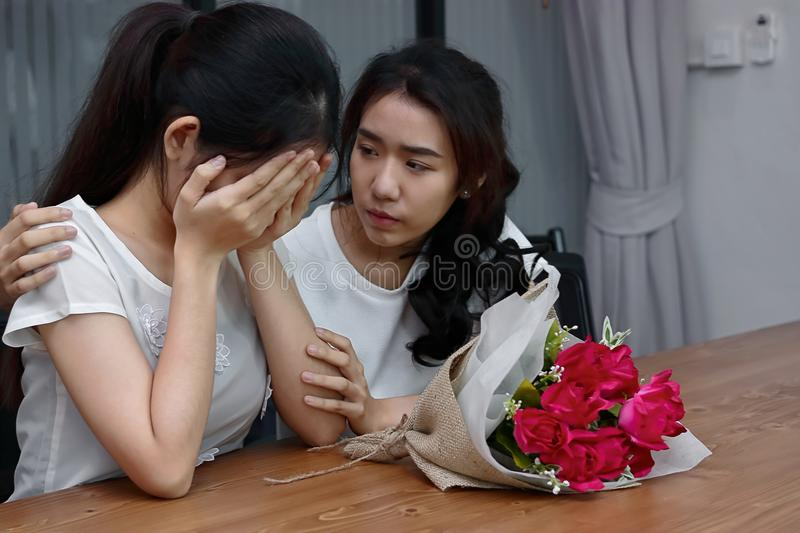 Exhausted stressed Asian woman comforting a sad depressed female friend. Break up or best relationship concept. Exhausted stressed Asian women comforting a sad royalty free stock photos
