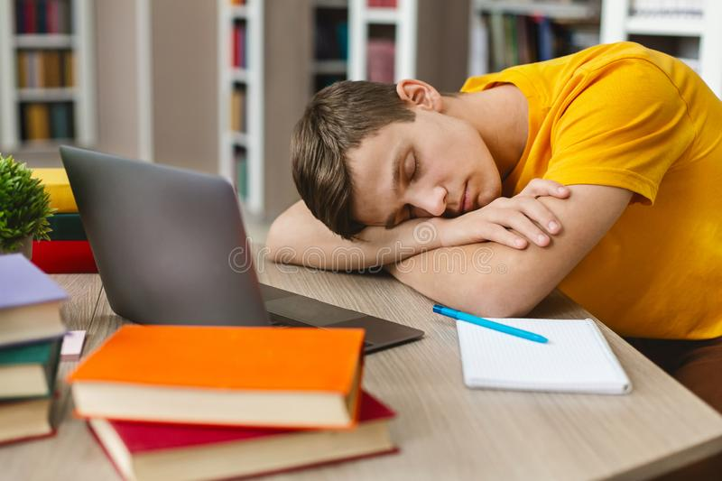 Exhausted student sleeping on workplace in front of laptop stock photo